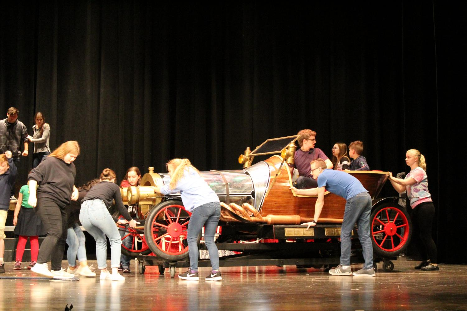 """Grandpa, played by sophomore Dominick Heyob, drives onto stage in """"Chitty Chitty Bang Bang,"""" followed by sophomore Maria Miller and freshman Gabe Means, who play old and crotchety inventors (Photo by Alexis Lee)."""